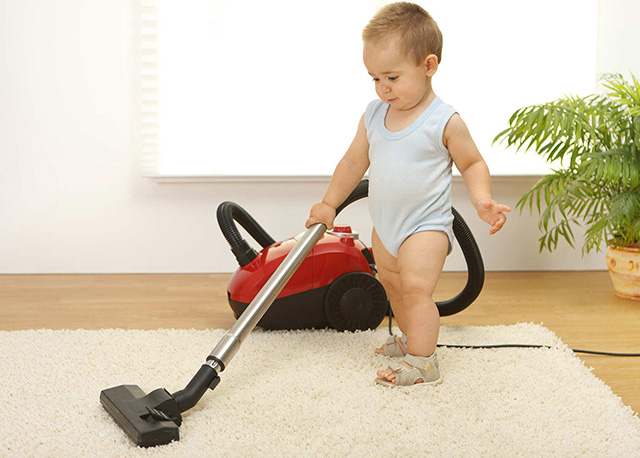 Picture of a baby vacuuming carpet and keeping it cleaning